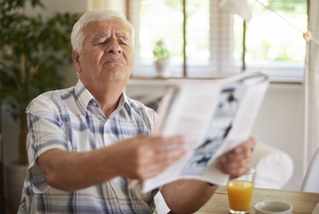 Man squinting while reading