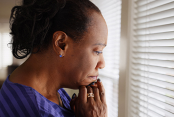 Woman looking sad out window